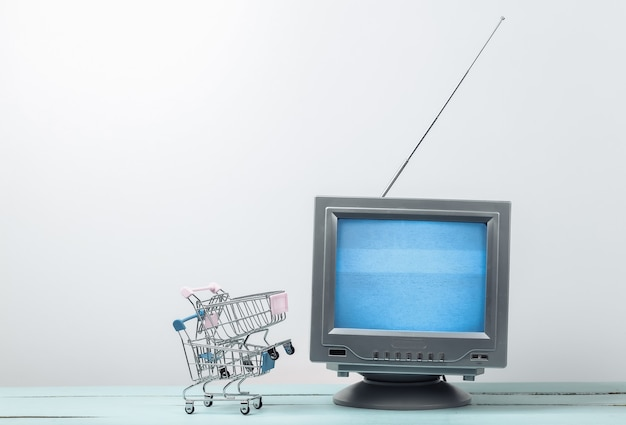 Tv shop. antenna old-fashioned retro tv with mini supermarket trolley on white wall