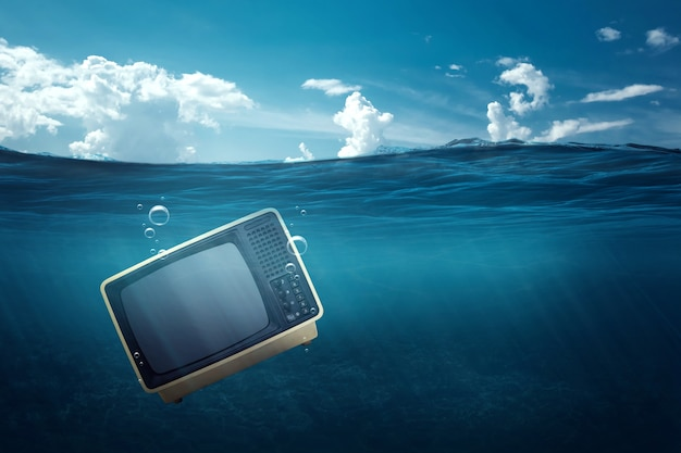 Tv sinks in the sea, tv crisis, tv under water. concept of crisis telecasting, internet, death of analogue broadcasting. copy space.