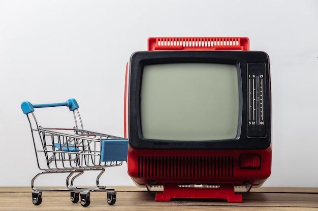 Супермаркет тв. тележка для покупок с ретро-телевизором на белом фоне