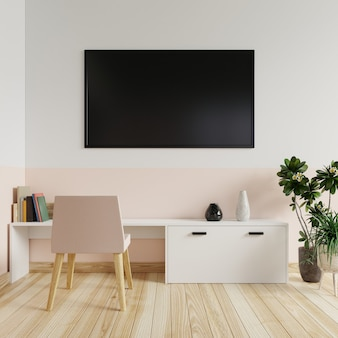 Tv on the wall in the living room with a chair and desk