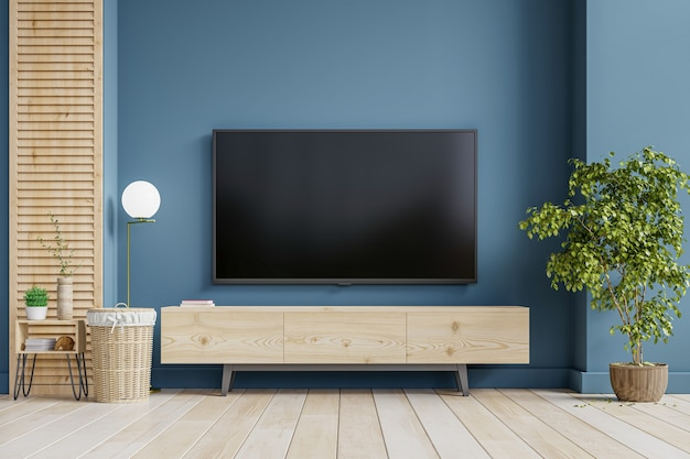 A tv wall mounted on cabinet in a living room room with dark blue wall