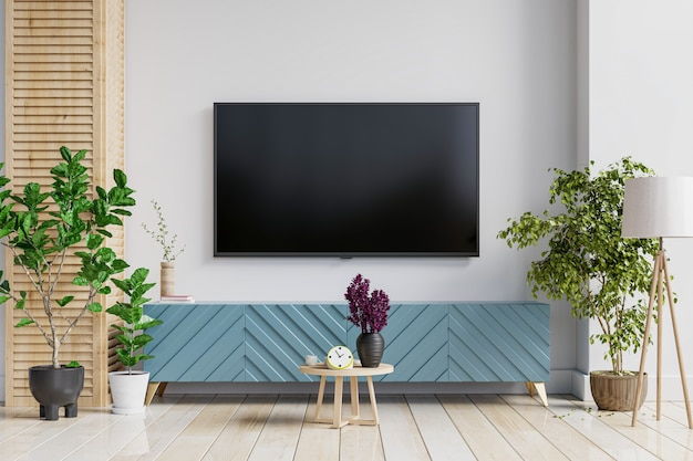 A tv wall mounted on cabinet in a living room room with a white wall