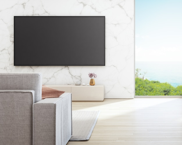 Tv on white marble wall against sofa in vacation home or holiday villa.