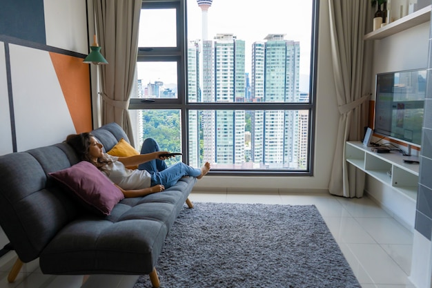 スタイリッシュなインテリアでソファの上の美しい退屈ブルネットの少女はテレビを見ています。手元のリモコンでtvチャンネルを切り替えます