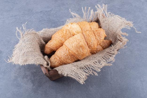 Tw свежий французский круассан в деревянной коробке.