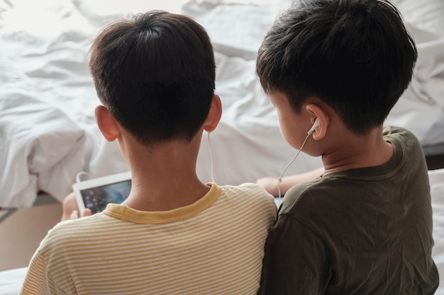 Tween boys using tablet and sharing earphones, listening to music, playing games, using internet technology