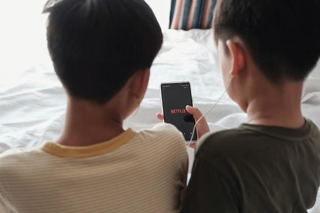 Tween男の子がイヤホンを共有し、スマートフォンでnetflixを見ている