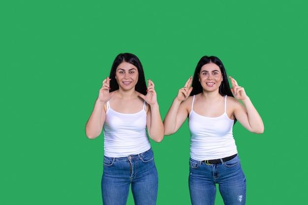 십대 소녀 녹색 배경 그들은 청바지와 흰색 셔츠 머리를 입고 검은 색 긴 소녀가 웃고 있습니다