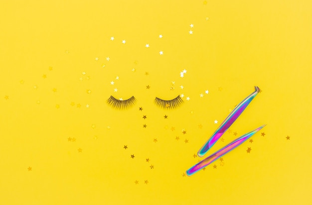 Tweezers for eyelash extension and artificial eyelashes on yellow