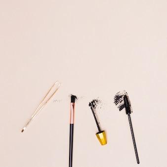 Tweezers; makeup brush; mascara brush isolated on beige background
