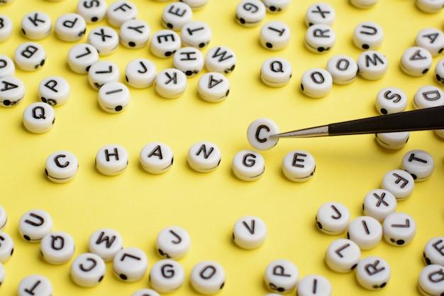 ピンセットは、単語changeに文字gの代わりに文字cを挿入します。白いプラスチックブロックで作られた単語の変更