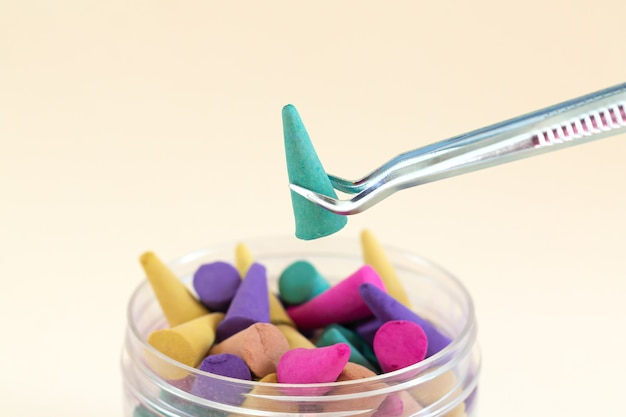Tweezers with aroma incense cone over colorful cones set close-up