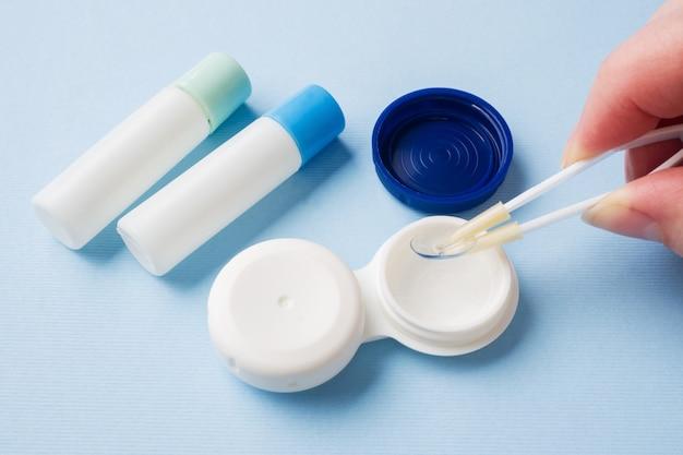 Пинцет с контактной линзой и пластиковый контейнер для хранения линз. закройте выборочный фокус.