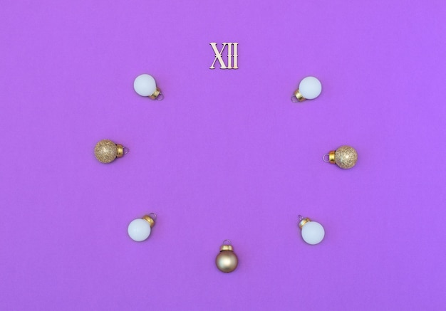 Twelve roman number with white and gold christmas balls in the form of a clock on purple background.