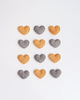 Двенадцать маленьких желто-серых полосатых текстильных сердечек на белом фоне