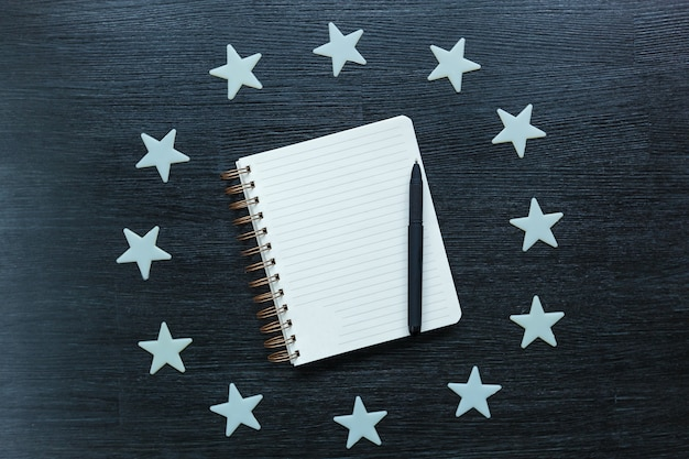 Twelve stars lay around a notepad with a pen on a black table. stars decoration.
