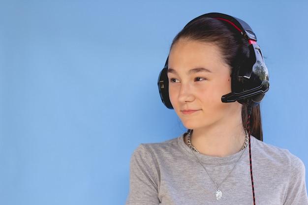 열두 살짜리 소녀는 파란색 배경에 헤드폰을 쓰고있다