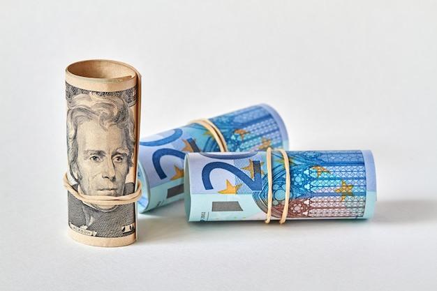 Свернутая двадцатидолларовая купюра, трубочка стоит рядом с двадцатью евро.