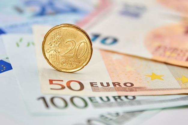 Монета 20 евроцентов на фоне банкнот евро