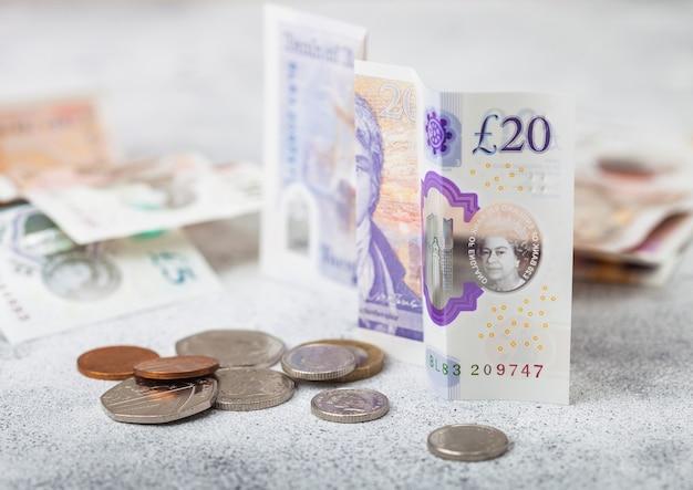 Банкнота 20 фунтов с монетой на светлой поверхности. концепция кризиса мировой экономики.