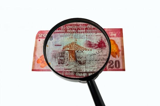 Twenty sri lanka rupees bill and a magnifying glass