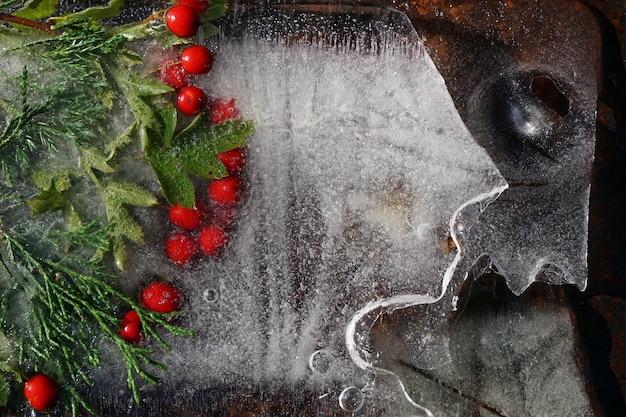 サンザシの赤いベリーと氷で凍結ジュニパーのtwifの背景