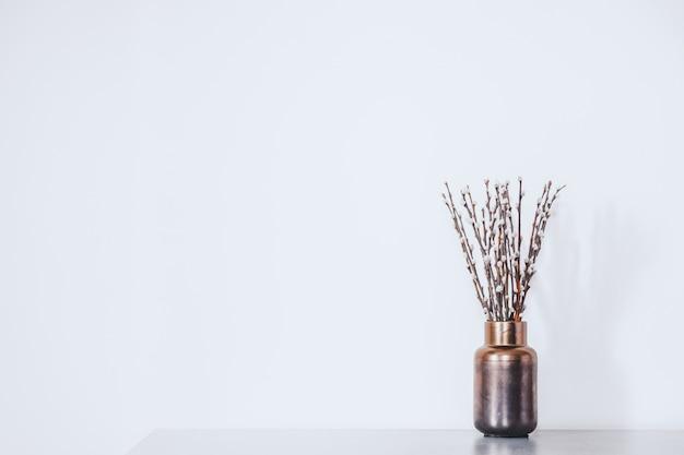 Веточки с бутонами в вазе против белой стене. концепция ранней весны, марта, пробуждения природы или предвкушения теплого сезона