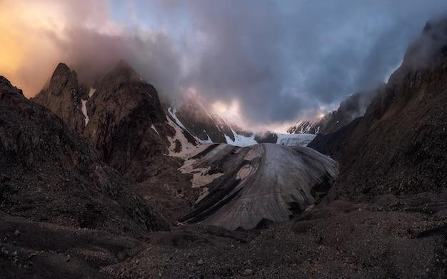 Сумеречные горы. величественный ледник освещен ярким золотым вечерним солнцем. панорамный вид. ледник большой актру, горный алтай.