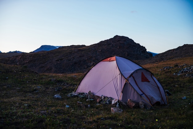 Twilight in mountains with tent on pass in violet light.