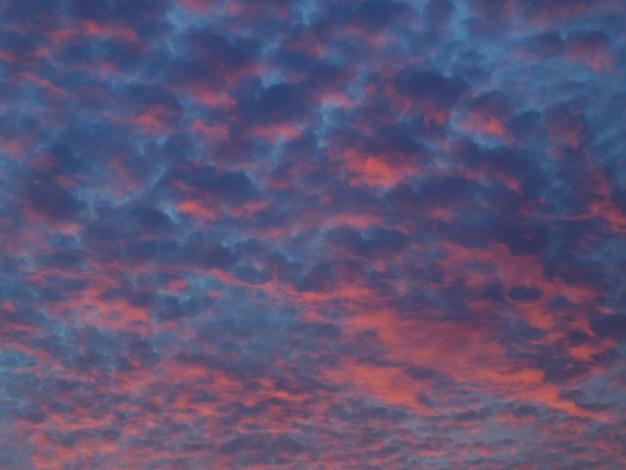 早朝の薄明の空、赤みがかった雲のある劇的な空。