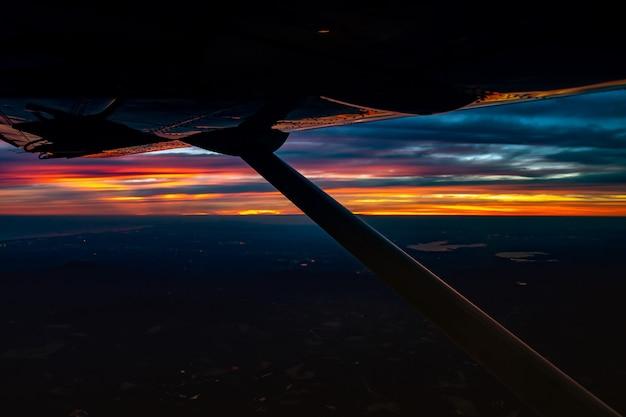 제트 비행기에서 황혼에서 밤까지 태국 도시의 불빛과 함께 붉은 오렌지색 푸른 하늘을 볼 수 있습니다.