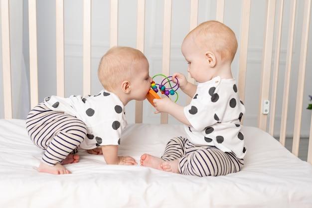 双子の赤ちゃんはベビーベッドで遊んで、1年までの子供の初期の発達