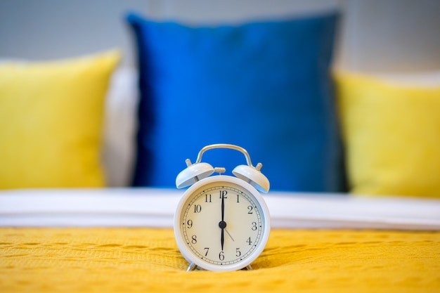 A twin bell alarm clock at 6:00 a.m. on bed in the bedroom.