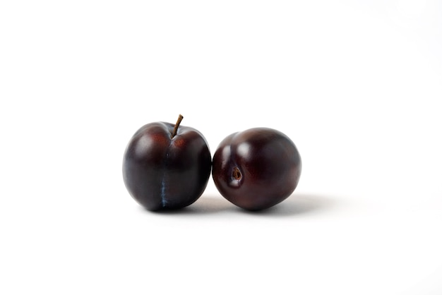 Twin black cherry plums isolated on white