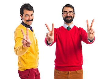 Twin brothers doing victory gesture