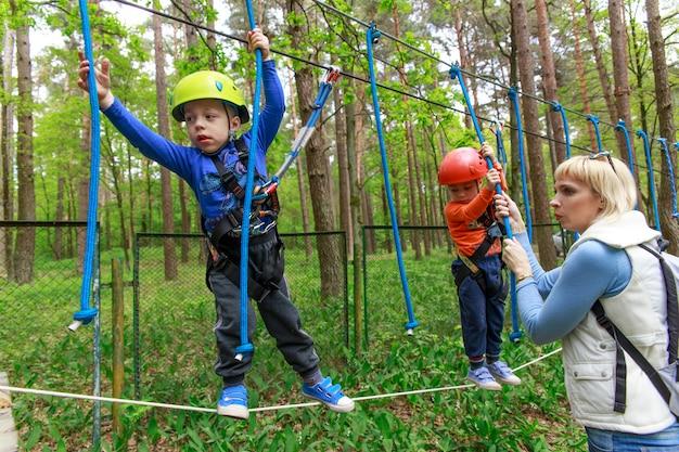 Twin brothers in helmet walks by rope