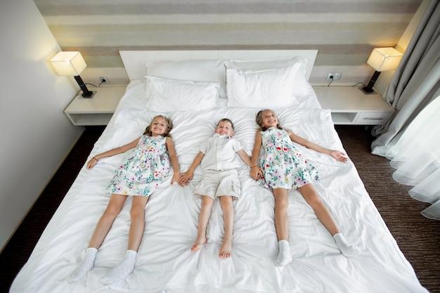 Сестры-близнецы и брат лежат на кровати в гостиничном номере