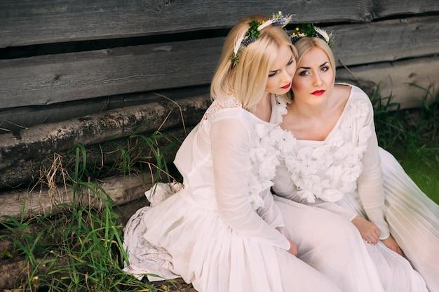 Twin sisters blowing dandelions