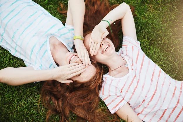 Сестры-близнецы, закрывая глаза от солнца, лежат на земле в летний день.