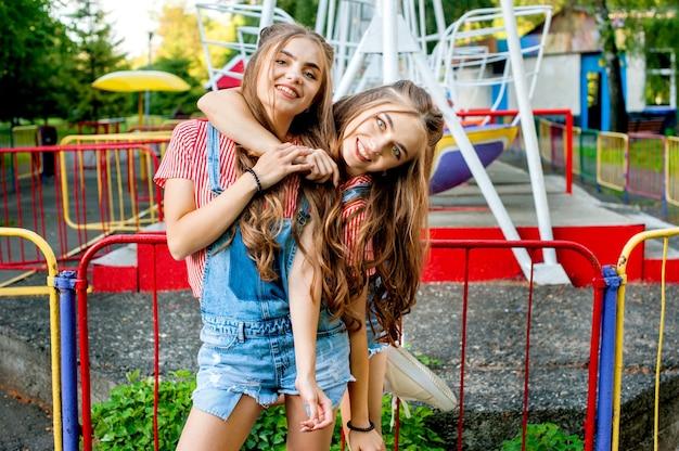 Сестры-близнецы в красочной обнимающей одежде, счастливые эмоции, с красочными качелями