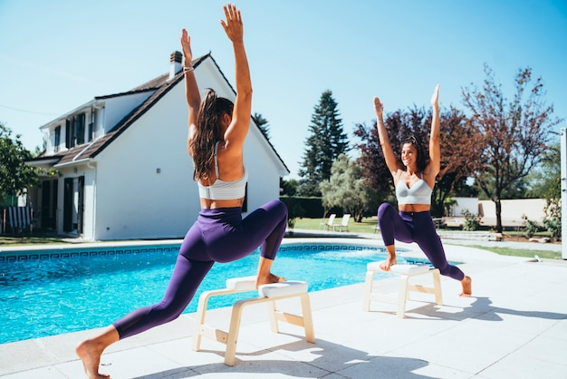 Twin sisters practicing yoga by a pool.