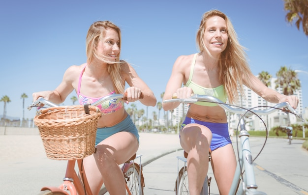 Twin sisters riding on bike in los angeles on the beach walkway