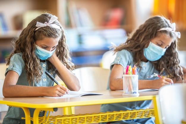 Covid-19 검역 기간 동안 학교에서 마스크를 쓴 쌍둥이 자매.