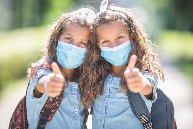 마스크를 쓴 쌍둥이 자매가 코비드-19 검역 기간 동안 학교로 돌아가 엄지손가락을 보여줍니다.