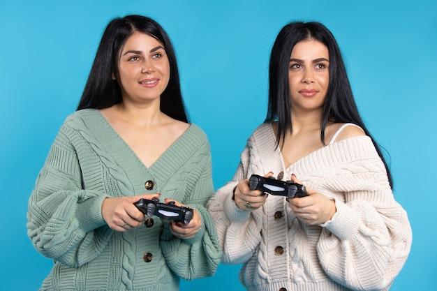 파란색 배경에 손에 조이스틱이 달린 쌍둥이 자매는 비디오 게임을하고 미소를 짓습니다.