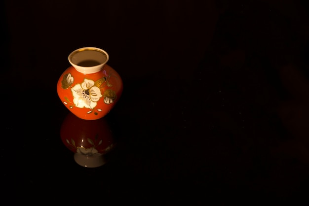 Twin vases, hand decorated with white flowers, placed on a black reflective surface