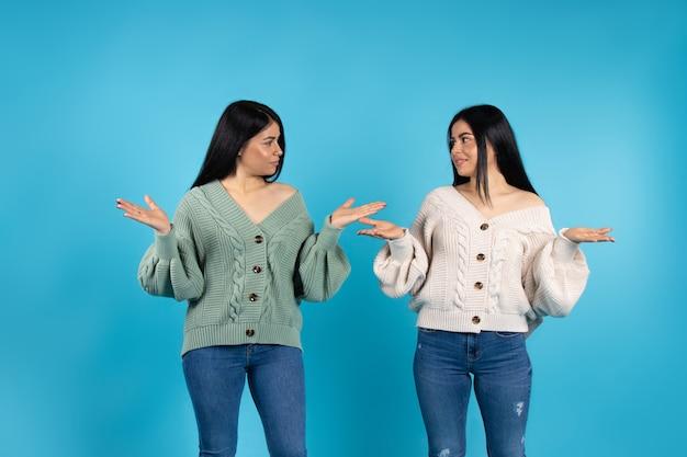 双子の女性は、お互いを見つめながら手のひらを横に広げます
