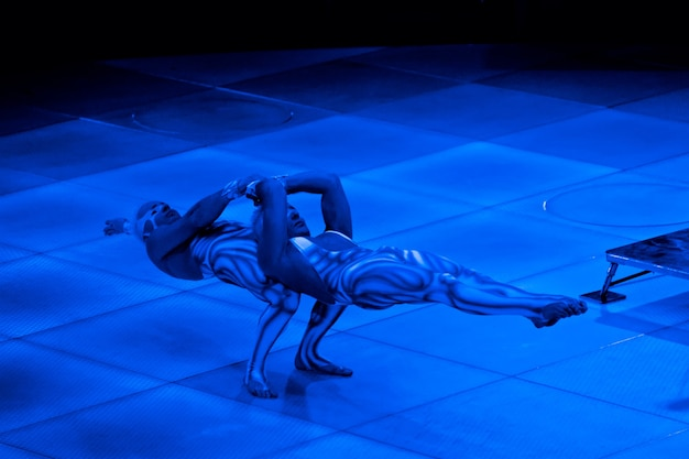 ネオン衣装を着た双子の曲芸師が腕に立って、紫外線メイク