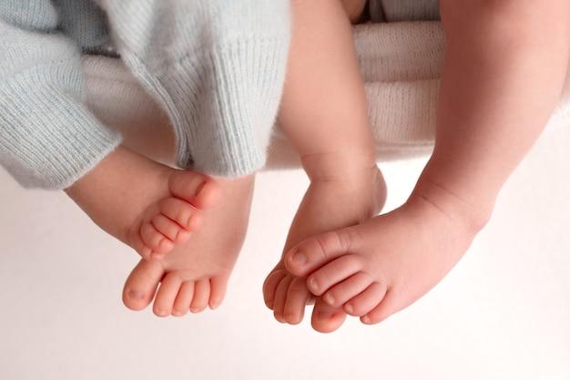 双子は赤ちゃんです。生まれたばかりの双子の足のクローズアップ写真。新生児の足と指。両親の手。父と母は子供の足を持っています。高品質の写真