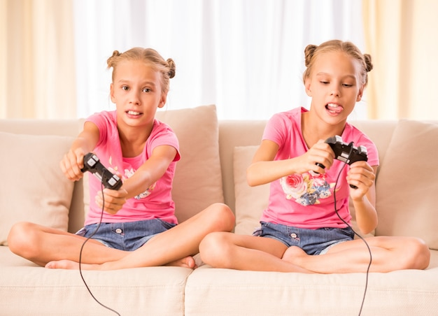 Twins are playing video game holding joysticks in hands.